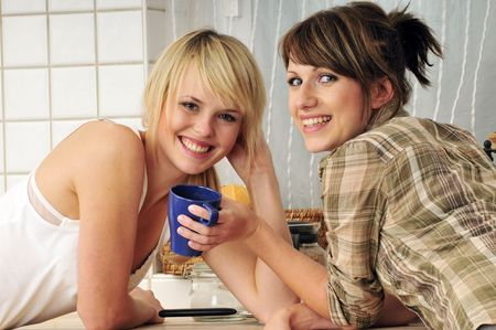 two girl friends drinking coffee a having a conversation photo