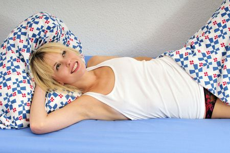 happy beautiful blond woman lying in bed smiling and daydreaming photo