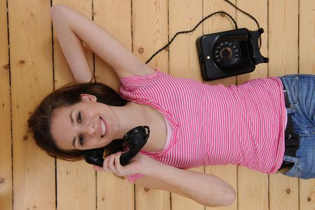 beautiful girl lying on the floor and talking on phone at home Stock Photo - 6569258