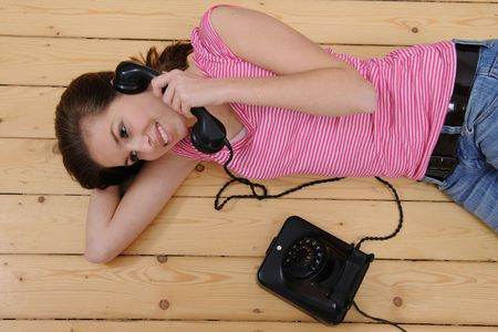 beautiful girl lying on the floor and talking on phone at home Stock Photo - 6569256