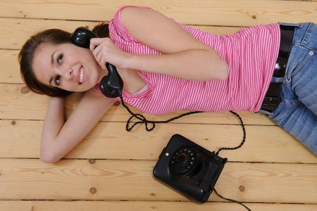 beautiful girl lying on the floor and talking on phone at home Stock Photo - 6569257