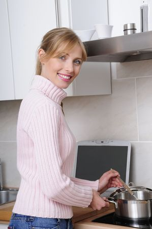 beautiful woman cooking using in a modern kitchen using the internet photo