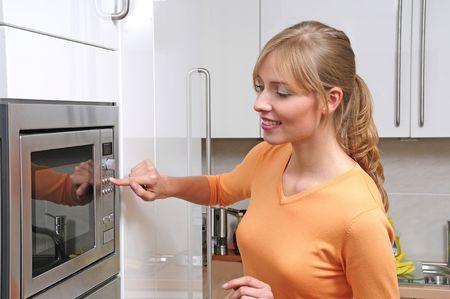 microwave oven: Mujer rubia con una cocina de microondas en una cocina moderna