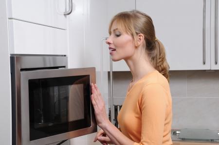 microondas: Mujer rubia con una cocina de microondas en una cocina moderna