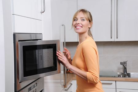 Blond woman cooks with a microwave in a modern kitchen photo