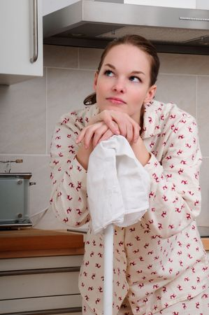 housewife in pajamas cleaning the kitchen and having an idea photo