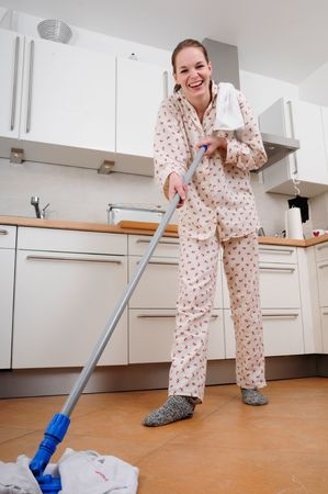 woman in pajamas cleaning the kitchen with a mop photo