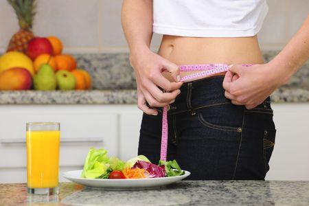 cintas metricas: mujer comiendo ensalada y frutas y la medici�n de su cintura  Foto de archivo