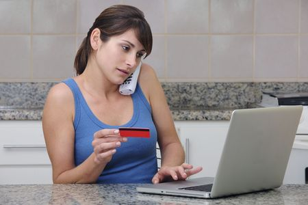 woman with creditcard calling on phone and using the internet