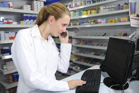 pharmacist using computer and telephone photo