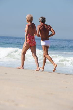 active senior couple on the beach photo