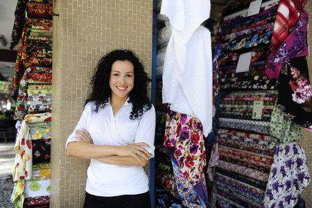 tienda de ropa: peque�as empresas: feliz propietario de una tienda de tejido Foto de archivo