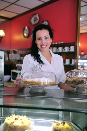 owner of a small business cake store cafe showing her tasty cakes photo