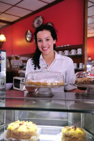 shop owner: owner of a small business cake store cafe showing her tasty cakes