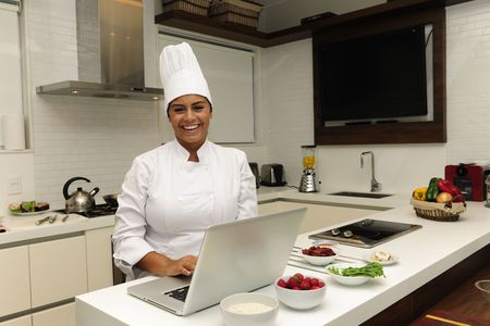 Happy chef cooking in kitchen and using laptop