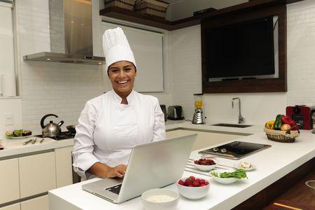 beleibt: Happy-Chef Kochen in der K�che und mit laptop Lizenzfreie Bilder