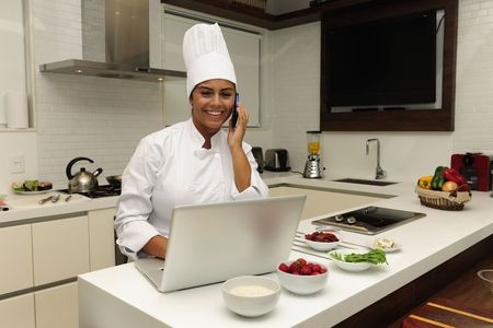 Chef cooking in kitchen talking on phone and using laptop photo