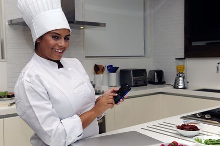 Happy chef cooking in kitchen and typing sms photo