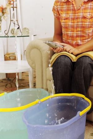 bursts: eaking tetto o tubo scoppio: donna chiamata assicurazione o idraulico Archivio Fotografico