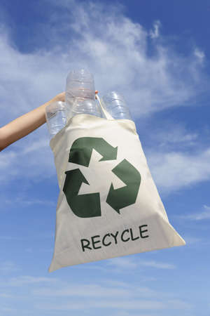 recycling: hand holding bag with plastic bottles against blue sky photo