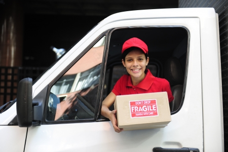 young delivery delivery courier in truck handing over package photo