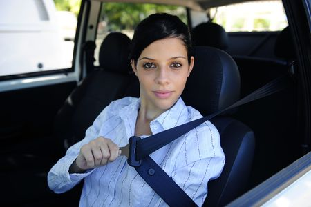 car safety: female driver fastening seat belt photo