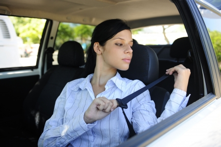 car safety: female driver fastening seat belt