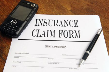 blank insurance claim form and pen on desktop with cellphone