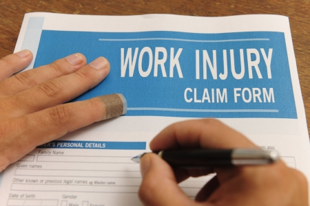 compensation:  insurance: blank work injury claim form with finger with plaster Stock Photo