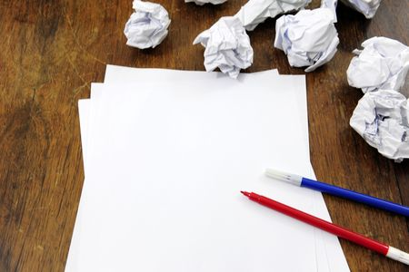brainstorming: empty paper on desk with many paperballs Stock Photo - 6831574