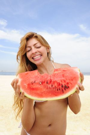 summer: blond woman eating watermelon on the beach photo