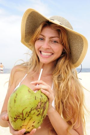 coconut drink: thirsty blond woman drinking coconut water on the beach Stock Photo
