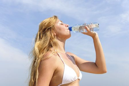 thirsty woman drinking water outdoors on a summer day photo
