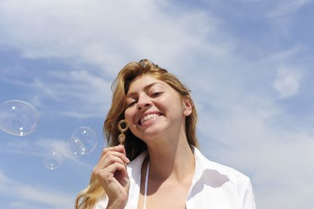 summer fun: blond woman blowing soap bubbles outdoors photo