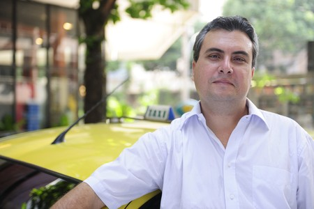 portrait of a taxi driver with cab photo