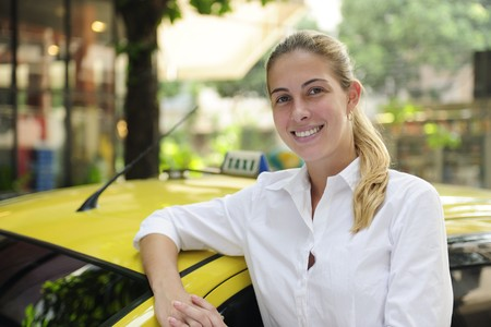 porait of a proud female taxi driver with her new cab photo