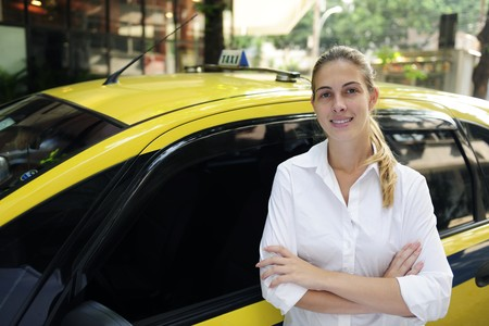 porait of a proud female taxi driver with her new cab Stock Photo