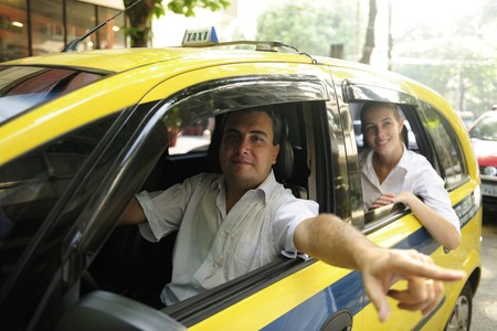 yellow taxi:  taxi driver showing passenger a landmark while driving