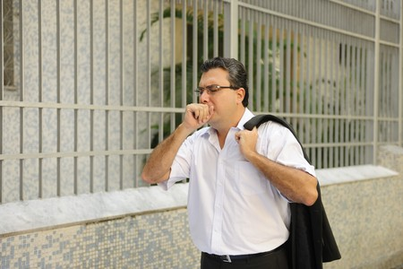 Influenza: Man coughing outdoors photo
