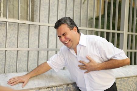 dolor de pecho: Dolor en el pecho repentino: hombre de tener un ataque al coraz�n el plegado  Foto de archivo