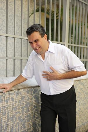Sudden chest pain: Man having a heart attack bending photo