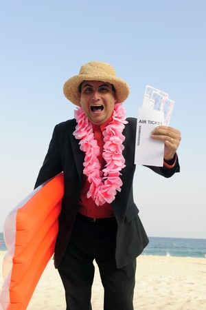 stereotype: ready  for  a  holiday: businessman on the beach with air tickets Stock Photo