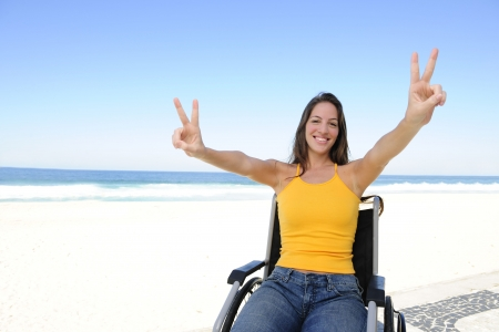 handicapped person: happy disabled woman in wheelchair outdoors beach showing victory sign