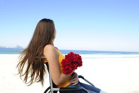 paraplegico: Romance: mujer en silla de ruedas con rosas rojas  Foto de archivo