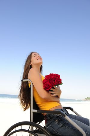 paraplegic: romantic love: happy woman in wheelchair with red roses