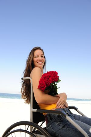 romantic love: happy woman in wheelchair with red roses photo