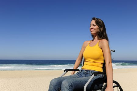 disability insurance: summer vacation: woman in wheelchair  enjoying outdoors beach