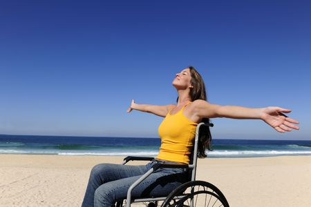 disability insurance: summer vacation: woman in wheelchair  sunbathing outdoors beach