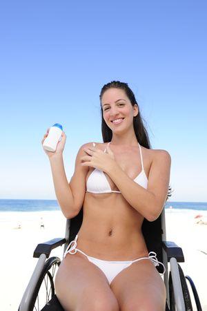 paraplegic: zomer vakantie: vrouw in een rol stoel sunscreen toe te passen op het strand Stockfoto