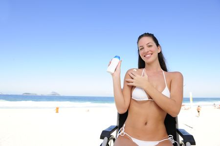 paraplegico: vacaciones de verano: mujer en silla de ruedas aplicar protector solar en la playa